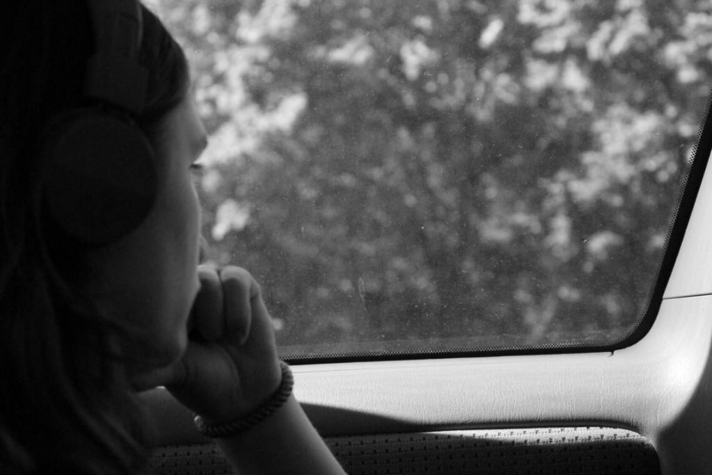Grayscale photo of a woman inside a car practicing intrapersonal communication.