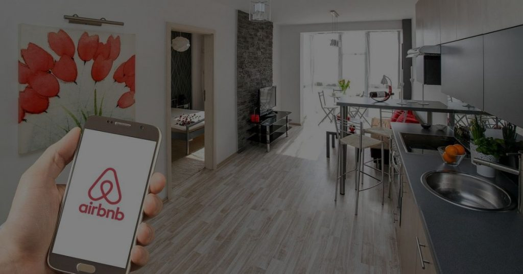 A picture containing a telephone with an Airbnb app and an indoor house. Disintermediation